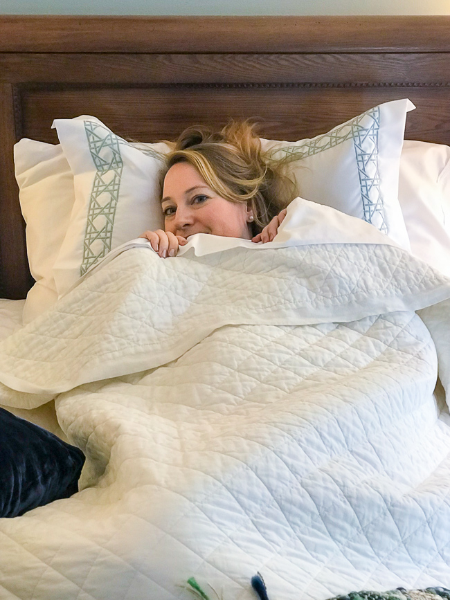 Woman peeps over bed covers.