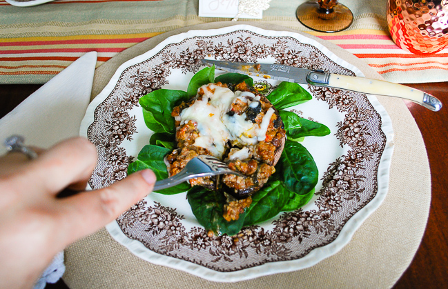 Cutting into sausage stuffed portobello mushrooms served on fall tablescape