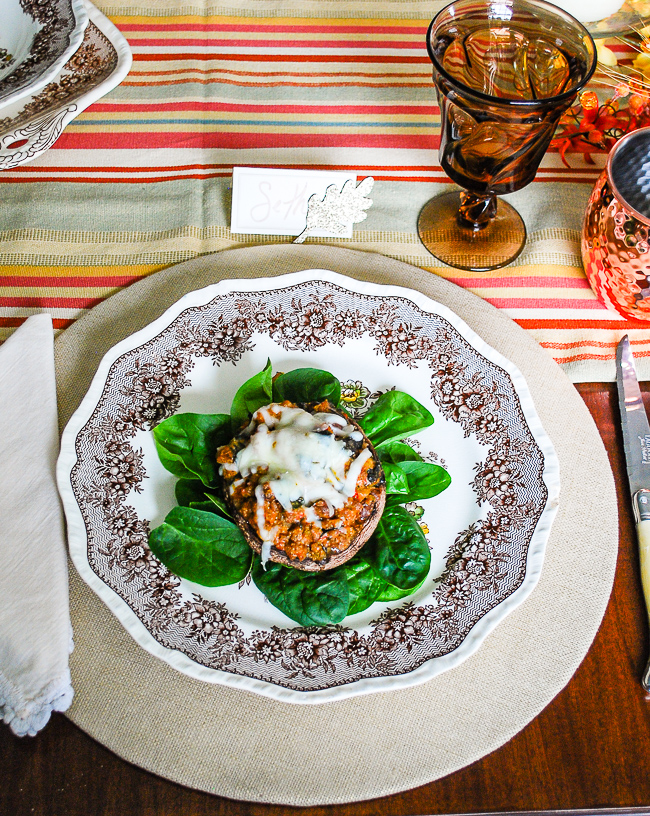 Sausage stuffed portobello mushrooms on bed of spinach.