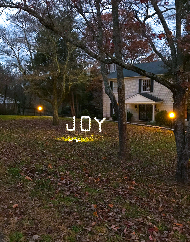 DIY outdoor Christmas decoration - PVC joy sign lit at night by spotlight in front of white brick house