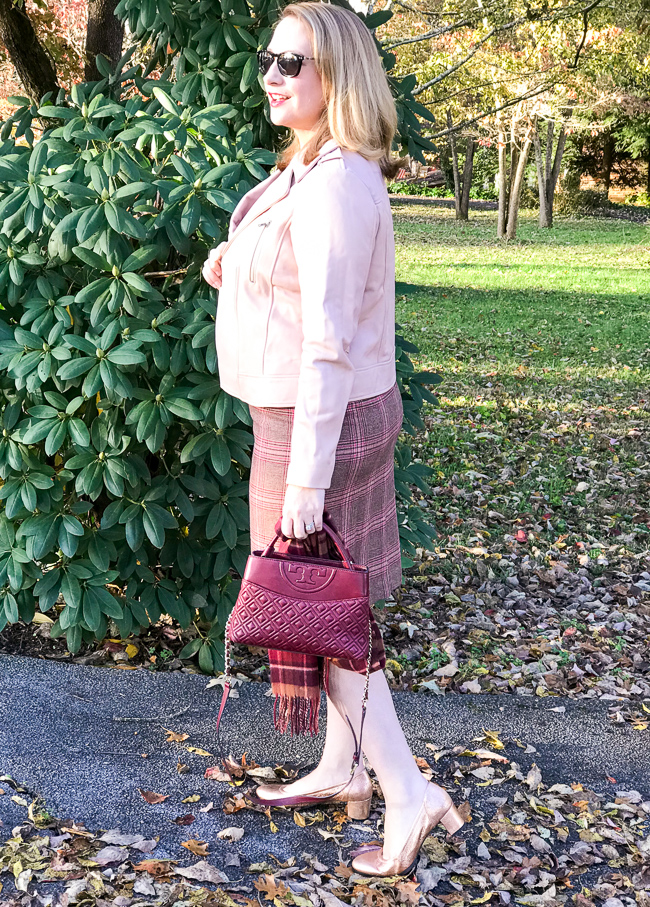 5 winter plaid pieces for work - blonde woman gazes in distance wearing pink moto jacket and plaid skirt