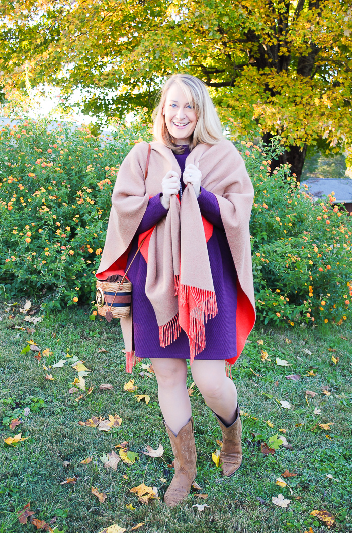 Blonde woman in the perfect purple dress from Joules poses in front of tree with yellow leaves