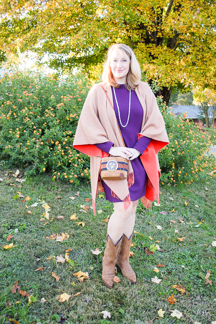 Blonde woman in the perfect purple dress from Joules and merino wrap poses in front of tree with yellow leaves