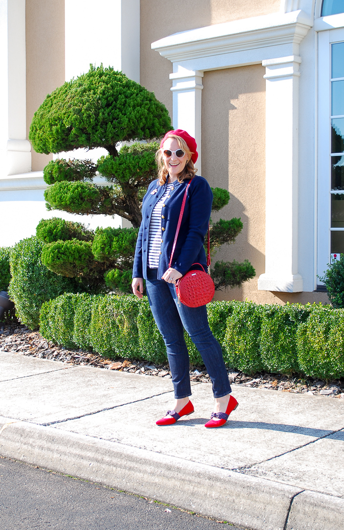 Woman wearing red beret and navy jacket with striped shirt and circle handbag for a red loves navy everyday chic look