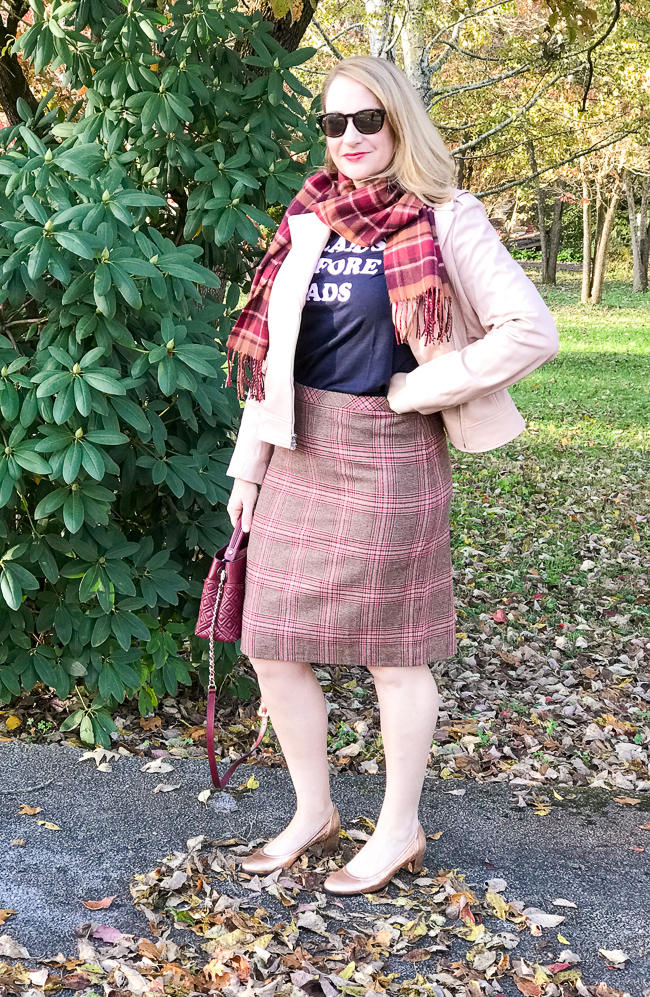 Blonde woman wearing pink moto jacket - graphic tee - and plaid skirt