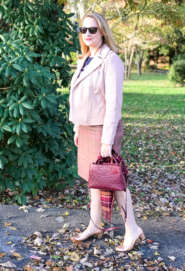 Blonde woman wearing pink moto jacket, plaid skirt, and tee for 5 winter plaid pieces you need in your wardrobe