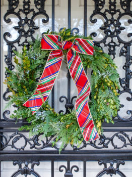 DIY Christmas wreath with fresh mixed greenery, including boxwood, cedar, and juniper hang on front door with plaid bow.