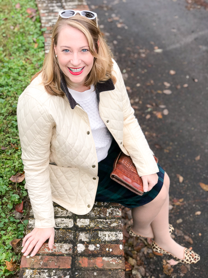 Casual holiday look with black watch skirt, Barbour coat, cable knit sweater, leopard print loafers, and leather clutch.