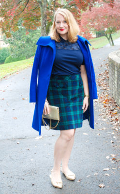 Blonde woman in dressy holiday look: black watch skirt, Draper James top, blue coat, and gold flats.