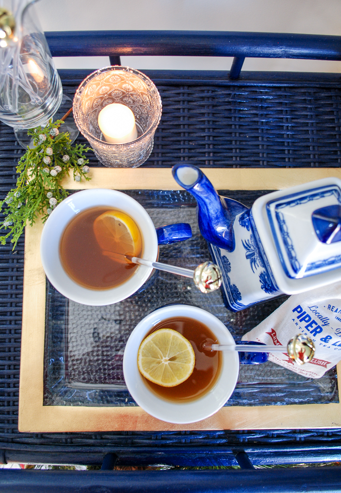 Overview of lemon berry hot toddy in blue and white porcelain on gold tray with jingle bell stirrers