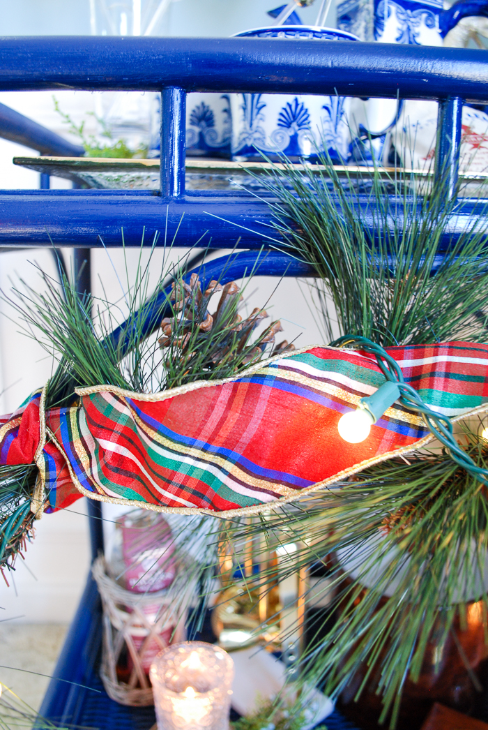 Plaid ribbon and pine garland with lights wrapped decorate a blue bar cart for the holidays
