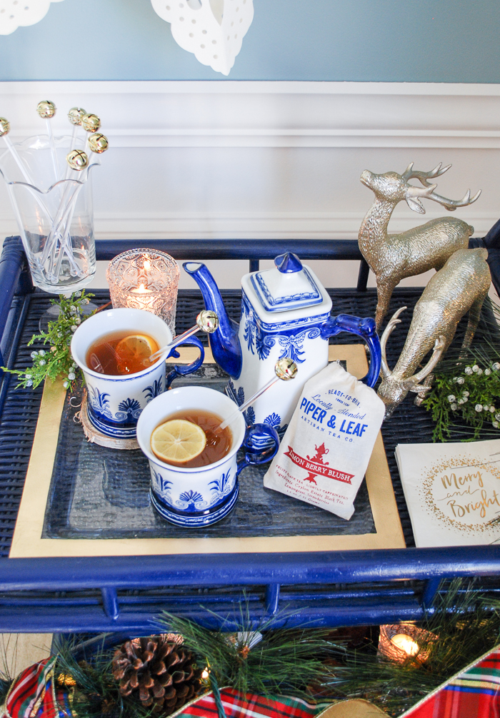 Lemon berry tea hot toddy in blue and white china on a blue rattan bar cart decorated for Christmas