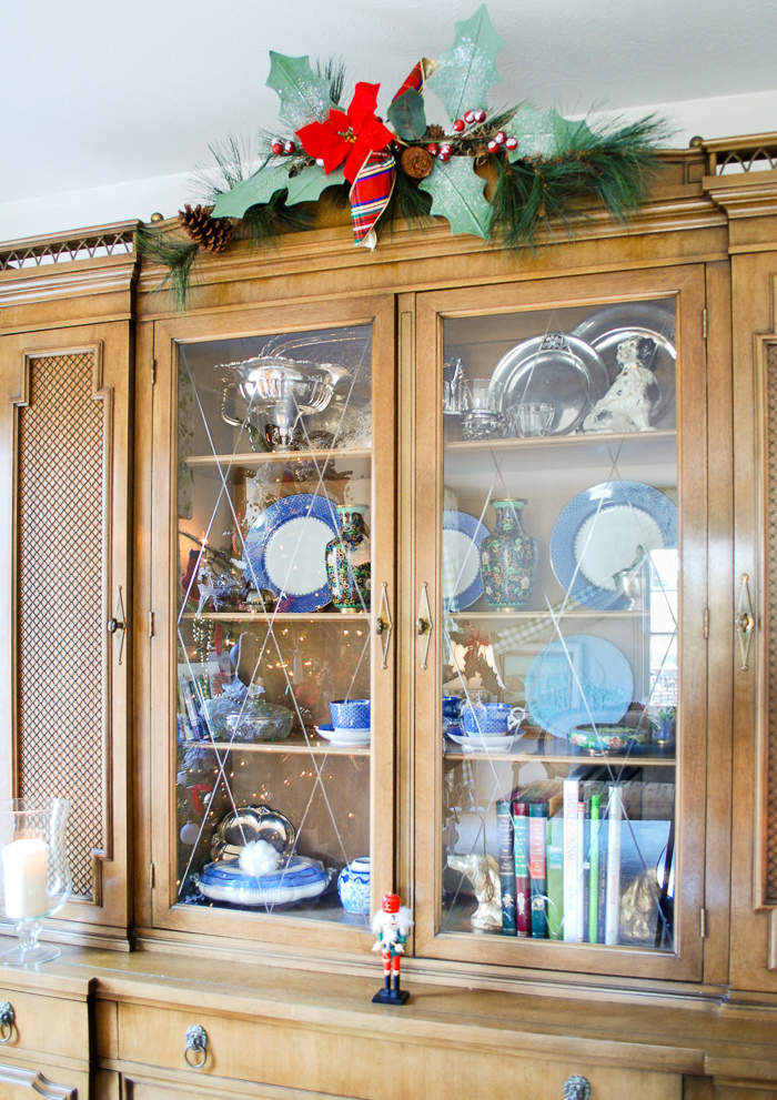 Antique bookcase decorated for Christmas with holly and pine topper