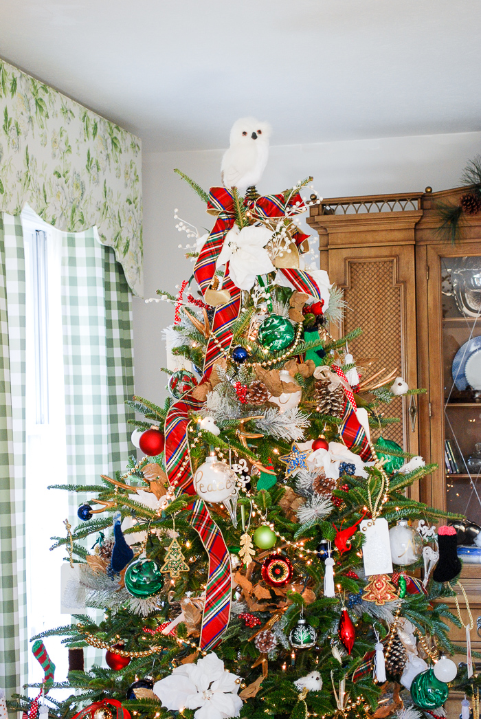 Preppy & plaid Christmas tree in front of window and bookcase in traditional living room trimmed with red and green plaid ribbon, poinsettia, snowy owl topper.