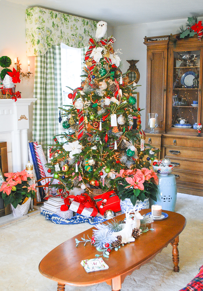 Preppy & plaid Christmas tree in front of window and bookcase in traditional living room trimmed with red and green plaid ribbon, poinsettia, vintage ornaments, and gold.