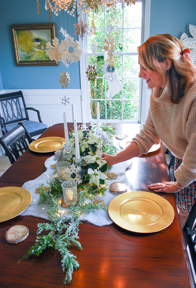 Winter tablescape tutorial - woman adjusts florals