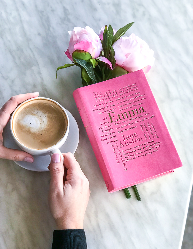 French cafe table with copy of Emma by Jane Austen, latte, and pink peonies