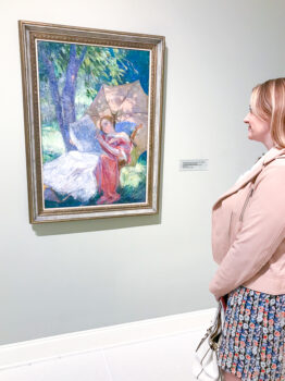 Blond woman gazes at impressionist painting of woman reading by Catherine Wiley