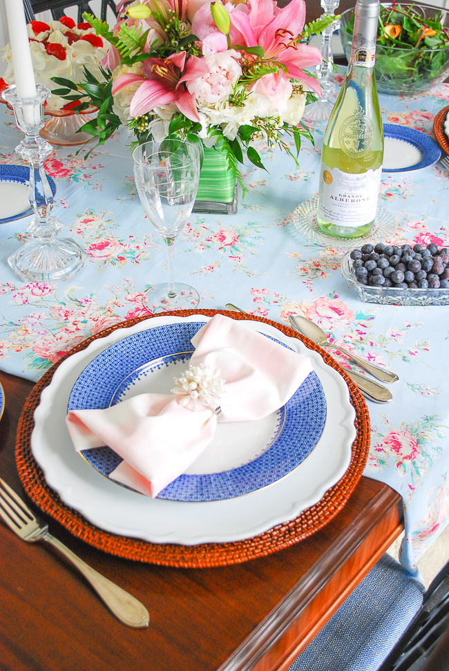 A feminine spring table setting with blue lace Mottahedeh china, rattan charger, and pink gingham napkin with pearl ring