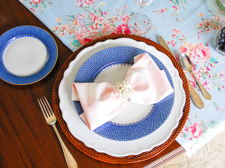 A feminine spring table setting with blue lace Mottahedeh china, rattan charger, and pink gingham napkin with pearl ring, and silver flatware