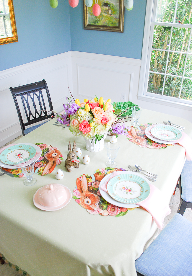 An Easter brunch table in pretty pastels with bunny placemats, antique china, etched stemware, and vibrant floral centerpiece