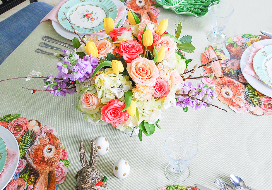 Vibrant floral centerpiece with pink roses, yellow tulips, hydrangea, pussy willow, and purple gillyflowers for a pastel Easter brunch table