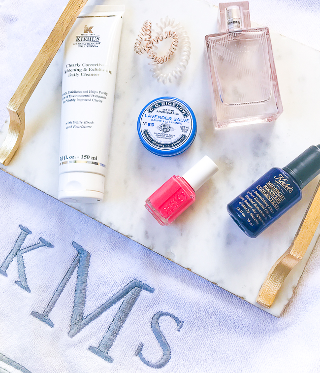 flatlay of 6 spring beauty must haves on marble tray with monogrammed towel