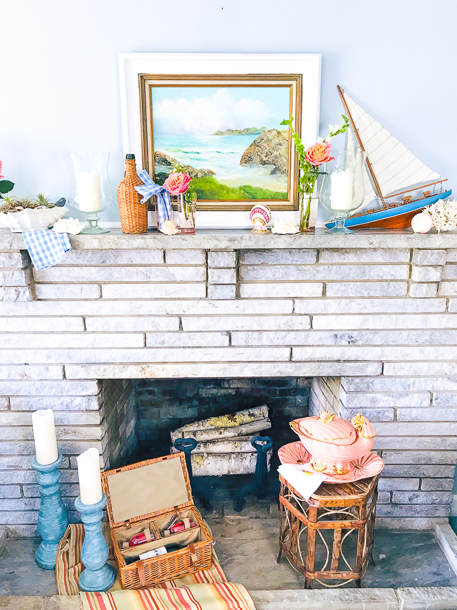 Get in a summer state of mind with this nautical summer mantel with vintage decor, featuring a sailboat, coral, seashells, and wicker.