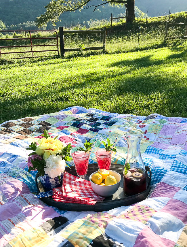 blueberry lemon mint fizz cocktails on a tray with peonies and patchwork quilt underneath