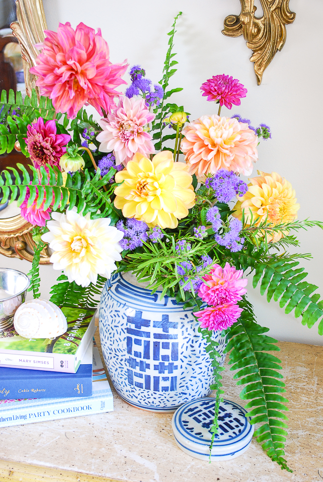 Blue and white ginger jar floral arrangement with dahlias and fern on antique sideboard with books