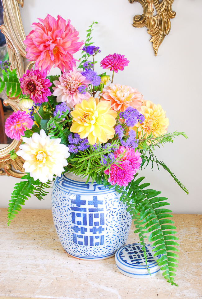 colorful dahlia arrangement in ginger jar with fern