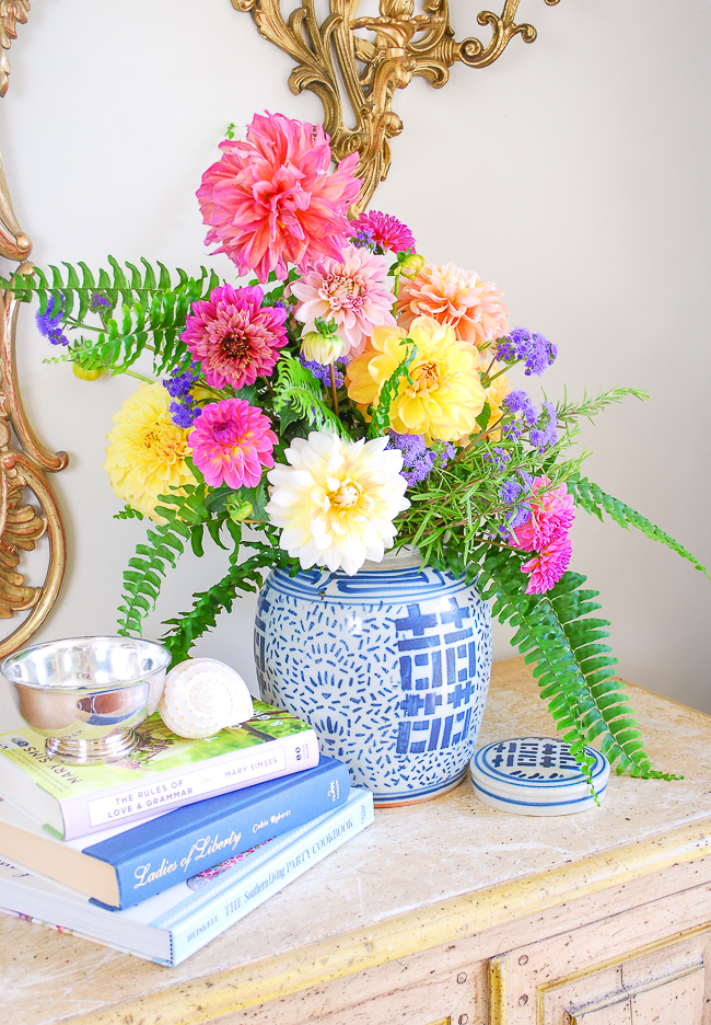 Pink and yellow dahlias merrily mix with fern and rosemary in this ginger jar floral arrangement
