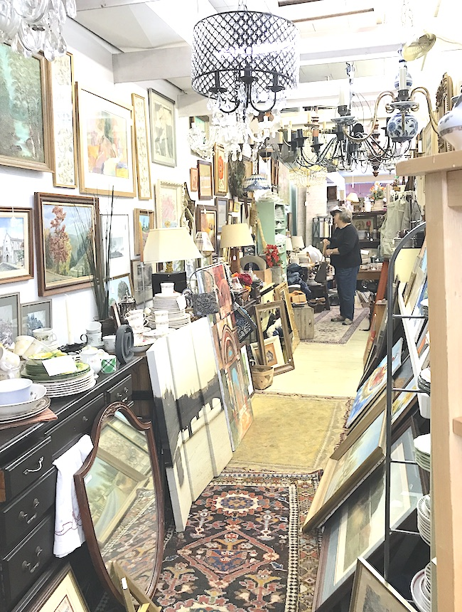 Jumble of art, ceramics, and lighting in antique store
