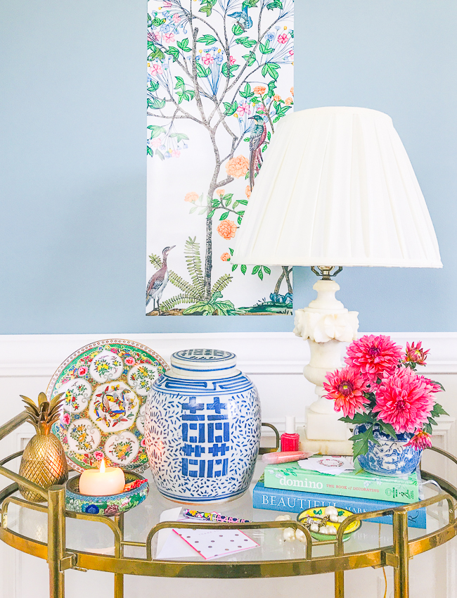 Affordable Chinoiserie decor on gold bar cart with fanciful landscape in background