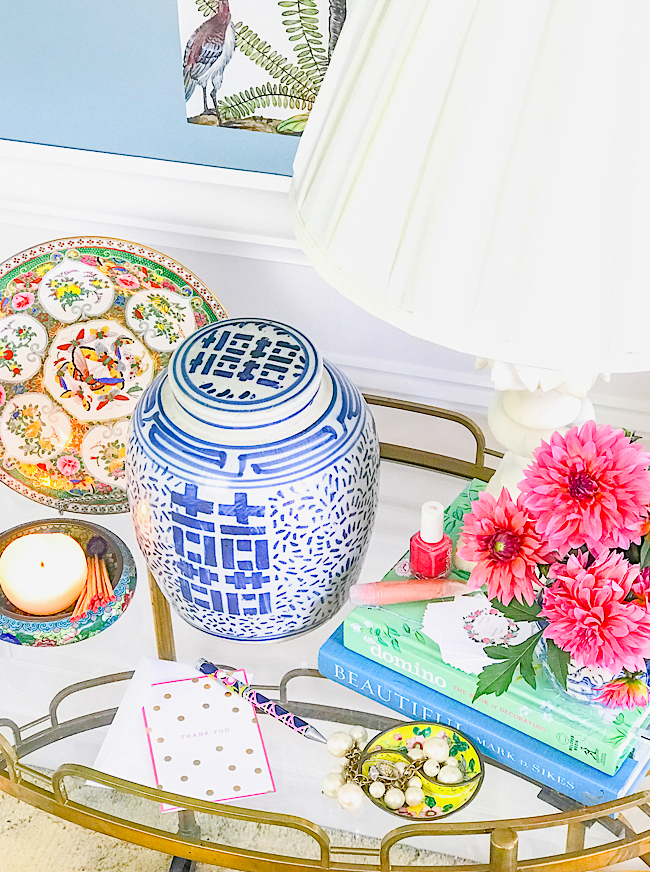 Top view of blue and white ginger jar with pink dahlias, marble lamp, rose medallion plate, and candle.