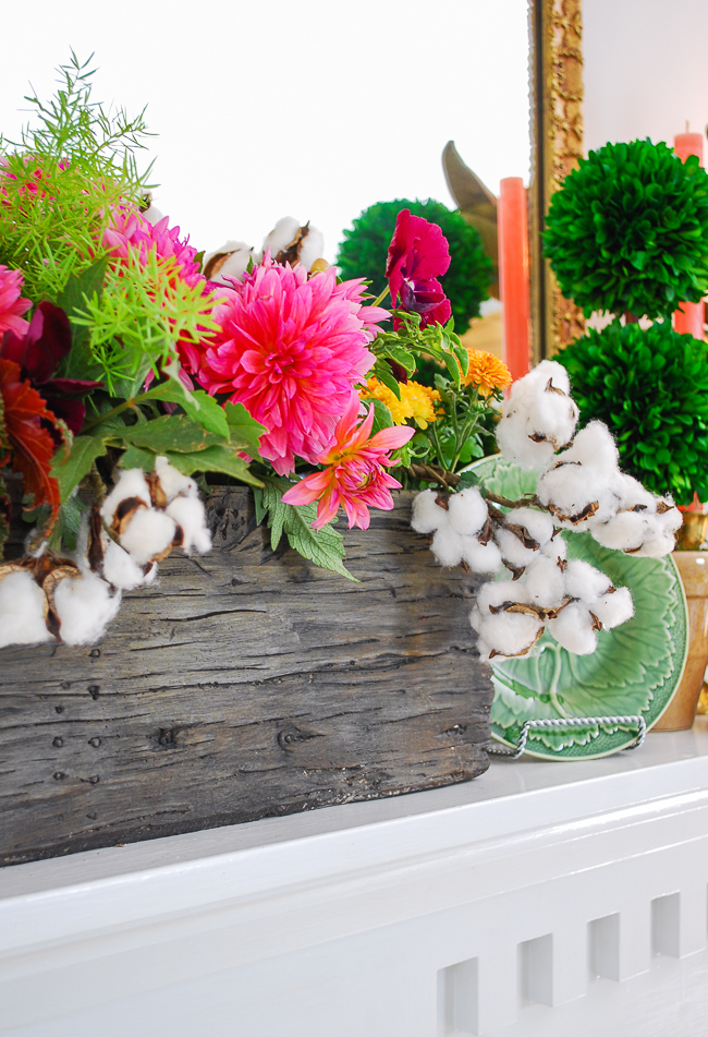 Fall dish garden in faux bois container centers fall mantel with majolica, magnolia, antlers, and cotton stems