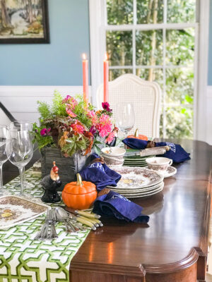 Fall dish garden with pink dahlias, mums, pansies, and fern on fall tablescape