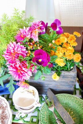 Purple pansies, pink dahlias, and yellow mums spill out of this fall centerpiece
