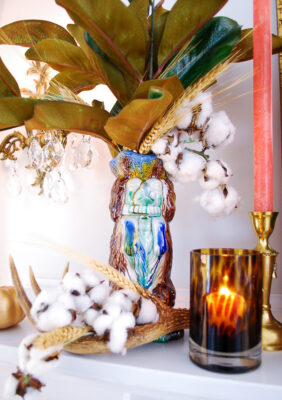 Majolica spaniel pitcher filled with magnolia, cotton, and wheat with tortoise shell candle holder