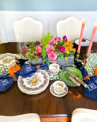 A Southern autumn table set with Mason's china, monogrammed napkins, fall florals, and trellis runner