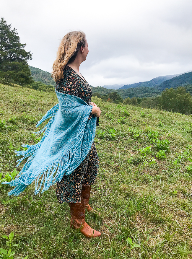 Katherine of Pender & Peony stands looking out at Blue Ridge Mountains in floral dress, boots, and wool shawl
