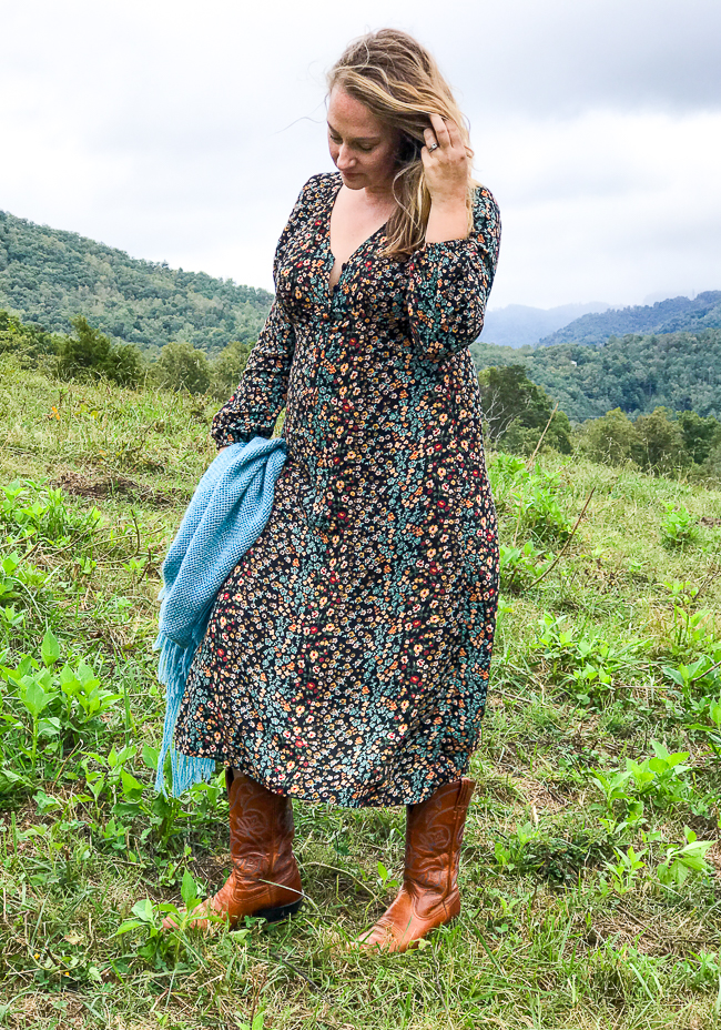 Katherine of Pender & Peony in floral dress holding shawl out for a walk in the pasture as a remedy for stress