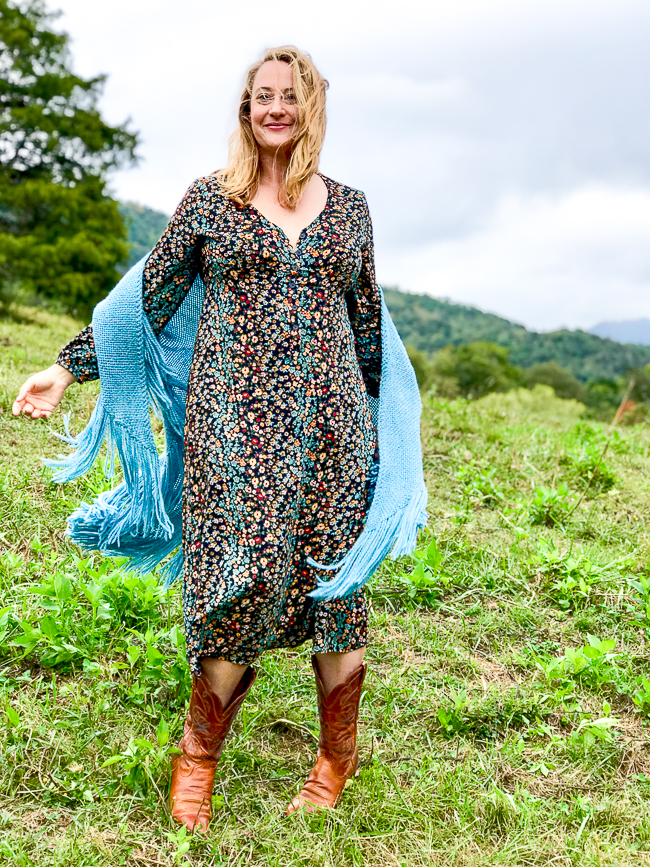 Katherine of Pender & Peony in fall floral dress and blue shawl dancing in field