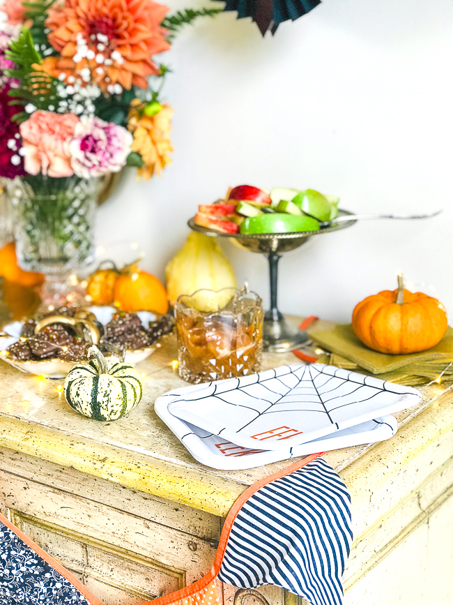 Eeeek plates, paper bats, and a flag garland decorate this Halloween treat bar filled with yummy desserts.