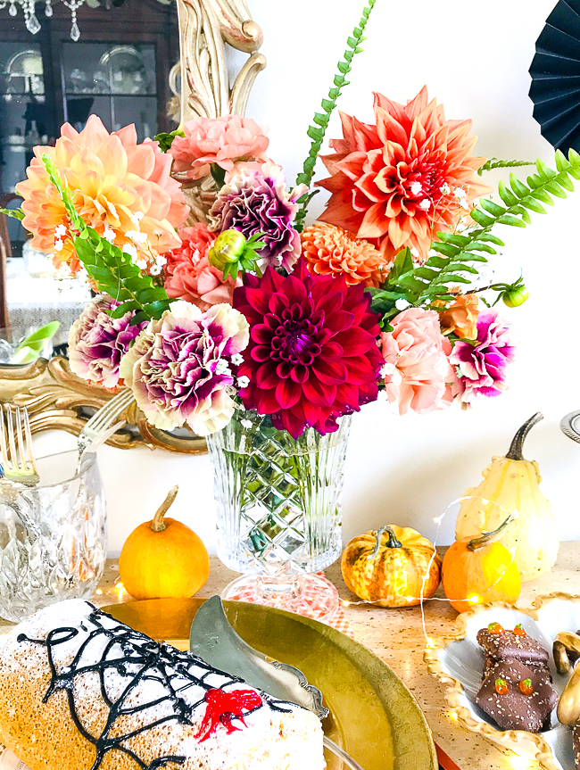 Orange, pink, and red dahlias and carnations add that floral touch to this Halloween dessert bar