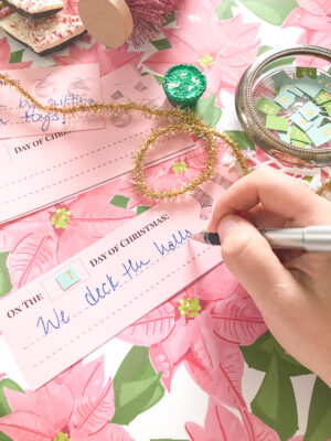 Writing out the Christmas activity slips on pink paper using the Pender & Peony printable
