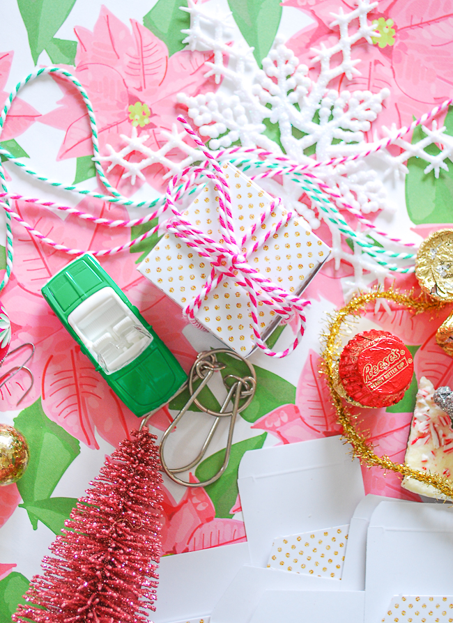 DIY advent calendar made with mini-gift boxes tied up with pink and white striped twine