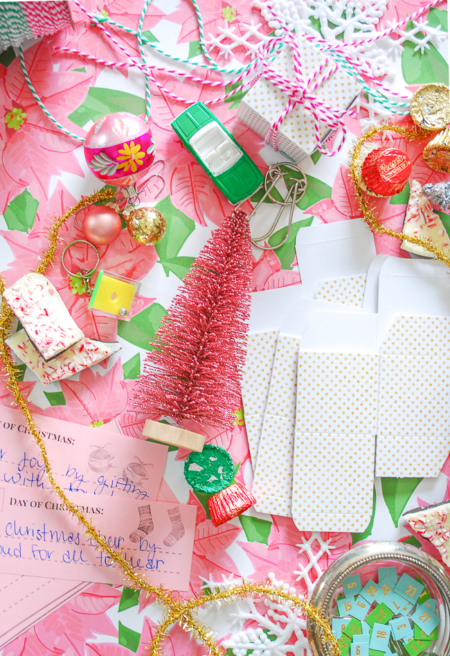 Boxes, candy, little toys, ornaments, and twine mingle on this poinsettia paper for the supplies to make these advent calendar present ornaments