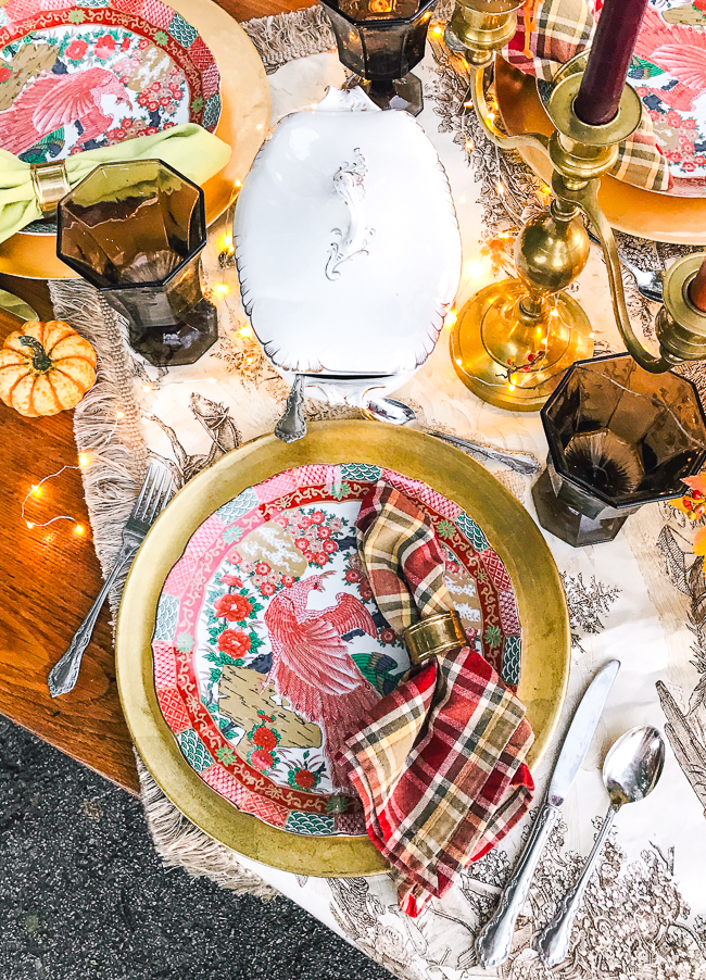 Japanese Arita peacock plates rest on gold chargers with plaid napkins and brown goblets for a rustic Chinoiserie Thanksgiving table.