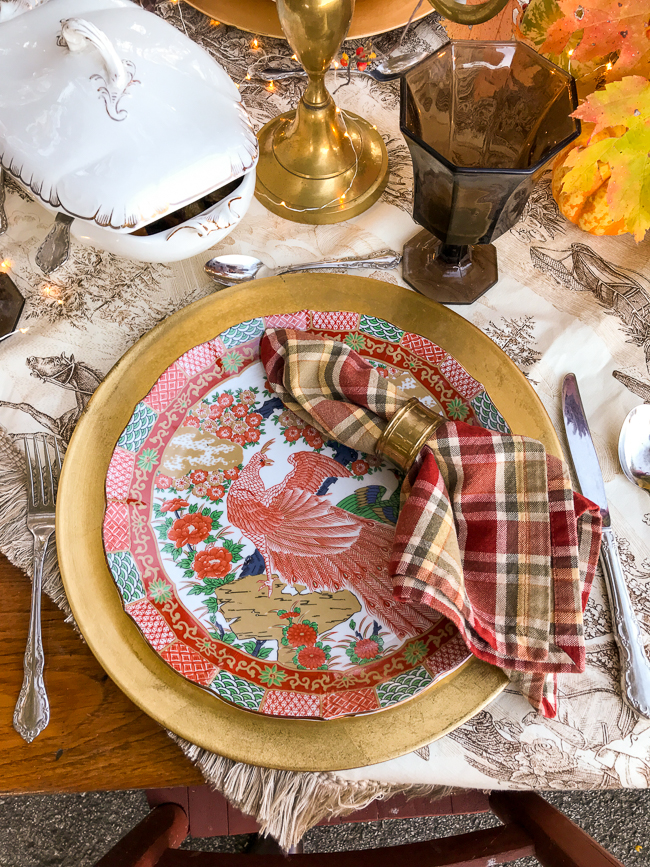 Thanksgiving place setting with Japanese Arita plate in Peacock pattern of orange and green on gold charger with plaid napkin and brown glassware.
